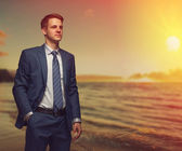 Office worker on the beach during sunset. — Stock Photo