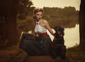 Retro style. The girl with a dog in a park in sunset rays. — Stock Photo