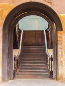 Ancient large wooden door with wooden stairs — Stock Photo
