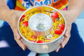 Hands of Woman hold bowl of water mixed with perfume and vivid flowers corolla , Songkran festival in Thailand — Stock Photo