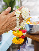 Woman hands hold vivid flower for Thai festival Songkran — Foto de Stock