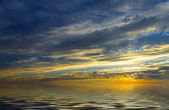 Incredible sunset, calm water and the sun, which setting in thunderclouds — Stock Photo