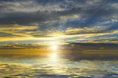Amazing view of the sun, filtering through the dark clouds over the quiet surface of the ocean — Stock Photo