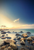 Lucid silky sea with many racks at sunset — Stock Photo