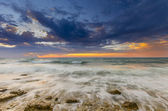 A fiery sunset and the waves lapping on the rocky shore — Stockfoto