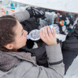 Stock Photo: Female snowboarder is drinking for quenching thirst