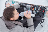 Female snowboarder is drinking for quenching the thirst — Stock Photo