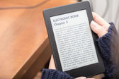 Reading a book with an e-book reader — Stock Photo