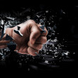 Concept. power fist coming out of cracked ground isolated on black background — Stock Photo