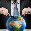 Greedy businessman cutting planet Earth — Stockfoto