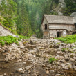 Wooden cottage in the mountains with creek — Foto de Stock