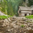 Wooden cottage in the mountains with creek — Stock Photo