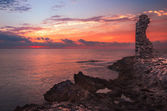 Sunset over the Sea and Rocky Coast with Ancient Ruins — 图库照片