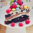 Triple chocolate cheesecake with raspberries and candies — Stock Photo