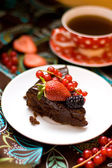Slice of chocolate cake decorated with chocolate frosting and fresh berries — Stock Photo