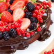 Close up of heart shaped chocolate cake decorated with chocolate frosting, strawberries, blackberries and red currant — Stock Photo