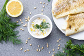 Sour cream sauce with lemon, parsley, fennel and roasted fish — Stock Photo