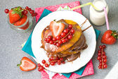 Pancakes with caramel sauce, red currant and strawberries and glass of milk on the grey background — Stock Photo