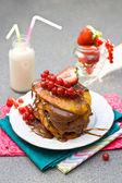 Naleśniki z sosem karmelowym, czerwone porzeczki, truskawki i szklankę mleka na szarym tle — Zdjęcie stockowe