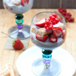 Vanilla pudding with vanilla seeds, fresh strawberries, red currant and savoiardi cookies in blue colored glasses — Stockfoto