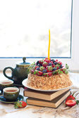 Napoleon cake, decorated with fresh berries, strawberries, blueberries and blackberries, with birthday candle. Two green tea cups and teapot near the window. — Stock Photo