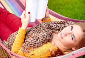 Young woman resting in a hammock and reading a book — Stock Photo