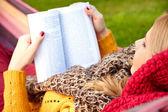 年轻女子躺在吊床上休息,读一本书 — 图库照片