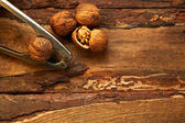 Walnuts and nutcracker on wooden background — Stock Photo
