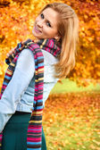 Beautiful woman standing in a park in autumn — Stock Photo