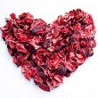 Dry red rose petals in heart shape isolated on white background  — Stock Photo