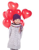 Cute little girl holding a bunch of red heart-shaped balloons — Zdjęcie stockowe