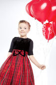 Cute little girl holding a bunch of red heart-shaped balloons — Stock fotografie