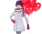 Cute little girl holding a bunch of red heart-shaped balloons — Stock Photo