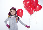 Cute little girl holding a bunch of red heart-shaped balloons — Stok fotoğraf
