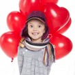 Cute little girl holding a bunch of red heart-shaped balloons — Stock Photo #36933303