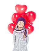 Cute little girl holding a bunch of red heart-shaped balloons — ストック写真