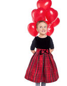 Cute little girl holding a bunch of red heart-shaped balloons — 图库照片
