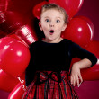 Surprised little girl holding a bunch of red heart-shaped balloo — Stock Photo