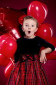 Surprised little girl holding a bunch of red heart-shaped balloo — Foto de Stock
