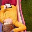 Stock Photo: Womis reading e-book lying on hammock