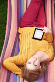 Woman is reading the e-book lying on the hammock — Stock Photo