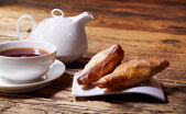 Morning breakfast - tea and croissant on wooden table — Stock Photo