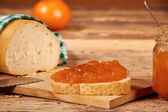 Tangerine jam with slice of bread on wooden table  — Stock Photo