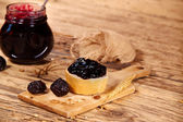 Jar of homemade plum jam on wooden table — Foto Stock