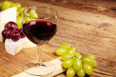 A red glass of wine and cheese — Stock Photo
