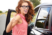 Successful young woman in the car with thumb up — Stock Photo