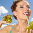 Happy young woman drinking kiwi juice over sky background — Stock Photo #49585885