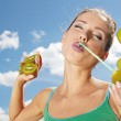 Happy young woman drinking kiwi juice over sky background — Stock Photo #49585933