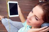 Młoda kobieta słucha muzyki na tabletki — Zdjęcie stockowe