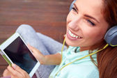 Young woman listens to music on tablet — Stock Photo